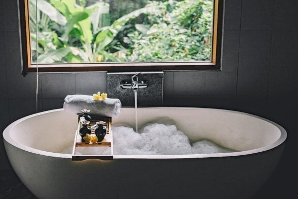 tips to make your bathroom cozier - a wooden bath tray